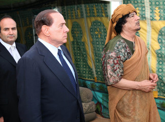 Italy's Prime Minister Silvio Berlusconi is greeted by Libya's leader Muammar Gaddafi on his arrival in Tripoli