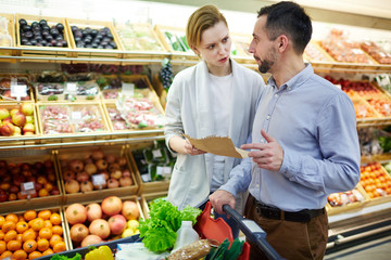 Portrait of adult couple arguing about shopping list while buying groceries in supermarket