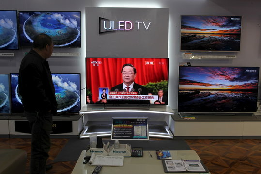 A man watches a TV screen showing live broadcast of Yu giving a speech during the opening session of the CPPCC, at a shopping mall in Kunming
