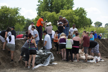 Residents pile sand bags along a river in Medicine Hat