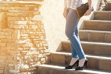 Woman in light blue jeans and black high-heeled shoes, holding clutch,walking on the stairs. Fashion wallpaper, with sunlight flash effect