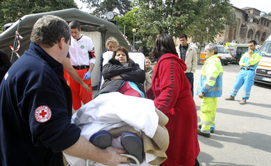 A woman is helped by rescue workers after an earthquake in Finale Emilia