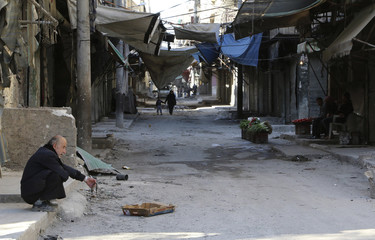 People sell vegetables as a man sits on a sidewalk in Aleppo