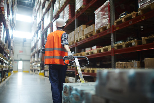 Worker in helmet and uniform pulling forklift with packed goods