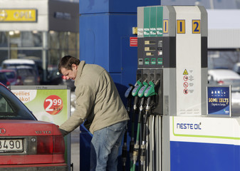 A man fills up his car at the Neste fuel station in Riga