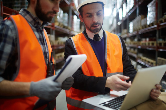Businessman showing data in laptop to warehouse worker