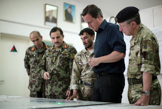 Britain's Prime Minister David Cameron and the Chief of the General Staff  David Richards look at a map of Helmand province during a visit to the Afghan National Army training camp at Camp Bastion, outside Lashkar Gahh, in Helmand Province, Afghanistan
