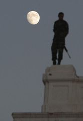 The moon is seen in the background as an anti-Gaddafi fighter stands guard atop a building during a celebration rally at Martyrs' Square in Tripoli