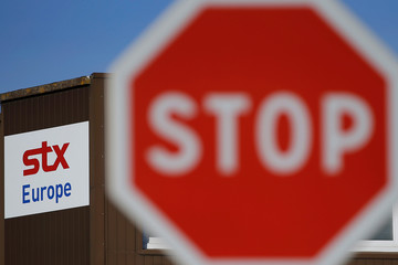 A stop road sign is seen near the logo of STX Europe at the STX Les Chantiers de l'Atlantique shipyard site in Saint-Nazaire