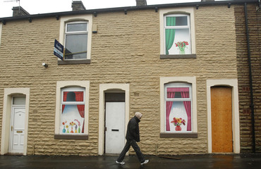 A man walks past empty houses with paintings of flowers and curtains used to hide the boarded up windows in Burnley
