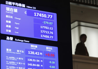 A man stands next to a stock quotation board displaying Japan's Nikkei average at the Tokyo Stock Exchange in Tokyo