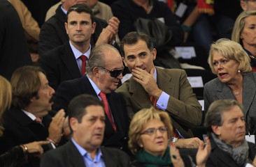 Spain's King Juan Carlos and Crown Prince Felipe chat during the Davis Cup final doubles rubber at the Olympic stadium in Seville