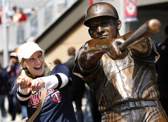 Minnesota Twins fan Hauschild mimics a statue honoring Twins great Killebrew before the Twins home opener against the Boston Red Sox at Target Field in Minneapolis