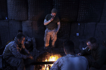 U.S. Marines from the First Battalion Eighth Marines Alpha Company gather round a campfire at their outpost in southern Afghanistan