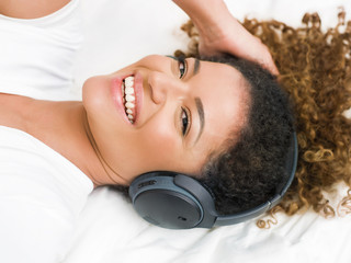 Gorgeous and happy woman listening to music and looking at camera