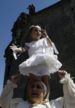 """A five-year-old girl, dressed in a traditional costume called """"Penlas"""", dances on the shoulders of a woman during the """"Coca"""" celebration in Redondela, the rural northeastern Spain"""
