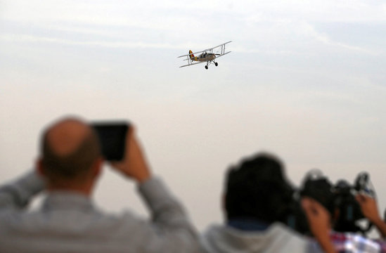 Photographers take a picture of the biplane flown by Cedric Collette and Alexandra Maingard as it glides by Egypt's iconic pyramids of Giza, on the second leg of their month-long journey through Africa in Cairo