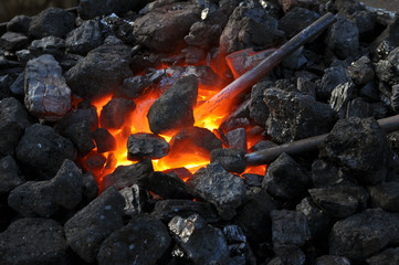 close-up  of a furnace,metal is heated in the forge on coals with hot flaming coal