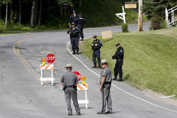 Law enforcement officers stand along County Route 41 during a search for an escaped prisoner south of Malone