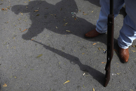 """Resident holds his 22 caliber rifle as he waits to handle it in during the """"Guns Exchange Program"""" in Monterrey"""