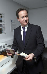 Britain's Prime Minister David Cameron holds passports during a visit to UK Border Agency staff, in Terminal 5 at Heathrow Airport, London