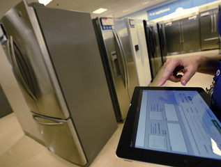 An employee uses a touch pad to enter information for a customer shopping  for a refrigerator at a Sears store in Schaumburg, Illinois, near Chicago