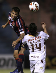 David Macalister Silva of Colombia's Deportes Tolima fights for the ball with Sergio Vergara of Paraguay's Cerro Porteno during their Libertadores Cup soccer match in Asuncion