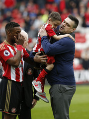 Sunderland's Jermain Defoe passes Bradley Lowery to his father after walking out with him before the match