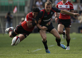 Wales' Prydie drops the ball as he is tackled by Japan's Tatekawa during their international rugby test match in Tokyo