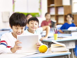 asian schoolboy using tablet in classroom