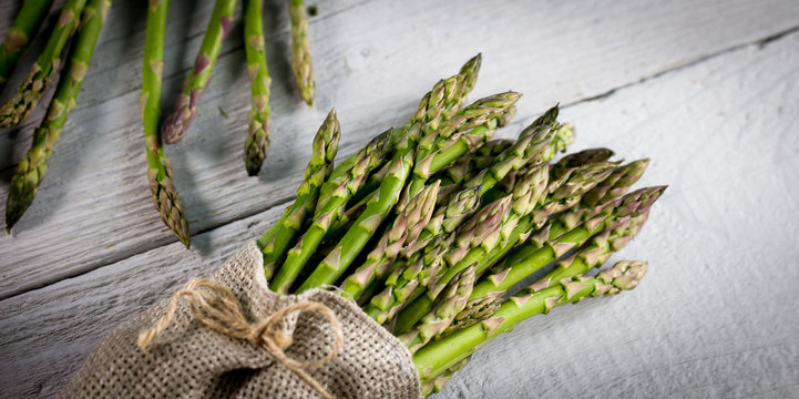 The Brunch of Fresh BIO Green Asparagus  on vintage wooden background. place for text