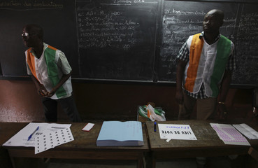 Polling officers, wearing shirts in the colours of Ivory Coast's national flag, wait for voters at a polling station in a school in Abidjan