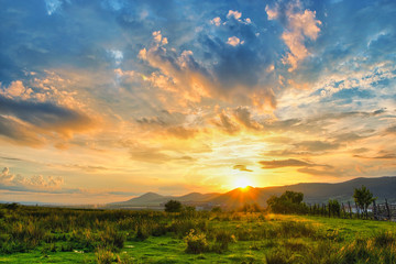 Rural sunset with colorful clouds.