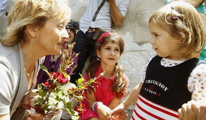 Swiss President Widmer-Schlumpf speaks to a girl during her visit to the southern Swiss village of Stampa