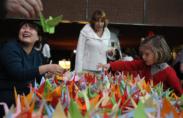 Helper fold paper cranes during a origami session called Senbazuru in favour of disaster victims in Japan in the Ahondiga cultural centre in Bilbao.