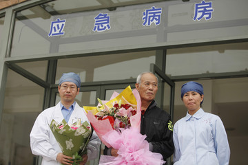 A man who was infected with the H7N9 strain of bird flu in early April holds a bouquet of flowers at the Shanghai Public Health Clinical Centre in Shanghai