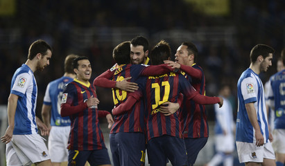 Barcelona players celebrate a goal by Lionel Messi during their Spanish first division soccer match against Real Sociedad at Anoeta stadium in San Sebastian