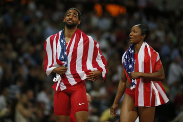 Jason Richardson of the U.S. talks to his compatriot Carmelita Jeter as they celebrate with their national flags following the men's 110m hurdles final during the London 2012 Olympics Games at the Olympic Stadium