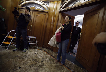 A woman shouts to journalists, asking not to take pictures of families of passengers aboard a missing Malaysia Airlines plane MH370, in front of a hotel room for relatives or friends of passengers aboard the missing plane, at a hotel in Beijing