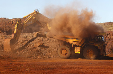 A trackhoe fills a dump truck in the South Limb pit at Atlas Iron's Pardoo mine, near Port Hedland