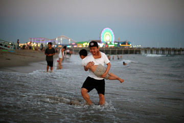 People cool off in the Pacific Ocean during a record-setting heat wave across the U.S. Southwest, on the summer solstice in Santa Monica