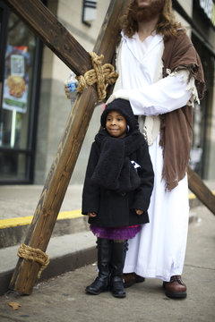 """Casey Green, 4, poses with Michael Grant, 28, """"Philly Jesus,"""" in a break from his carrying a 12 foot cross 8 miles through North Philadelphia to LOVE Park in Center City as part of a Christmas walk to spread the true message of the holiday in Philadelphia"""