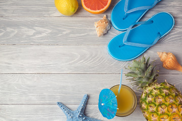 Tropical summer vacation background with pineaplle, juice and flip flops on wooden table. View from above. Flat lay