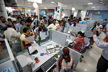 People stand in queues at cash counters to deposit and withdraw money inside a bank in Chandigarh