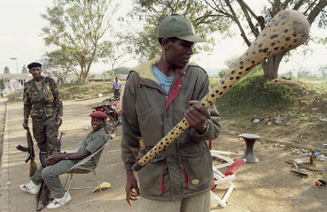 File photo of a Rwandan Patriotic Front rebel observing a nail-spiked club found near a militia checkpoint in Kigali