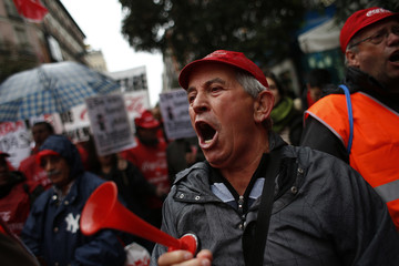 Coca-Cola employees and supporters shout slogans during a protest against the closure of four Coca-Cola bottling plants and job cuts in Spain as they march in Madrid
