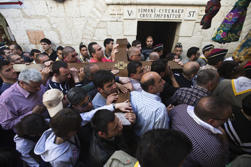 Worshippers carry a cross as they pass the fifth station of Via Dolorosa in Jerusalem
