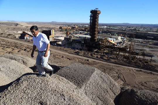 A man walks in front of a prilling tower inside an old SQM nitrates plant as the town of Maria Elena is seen in the background