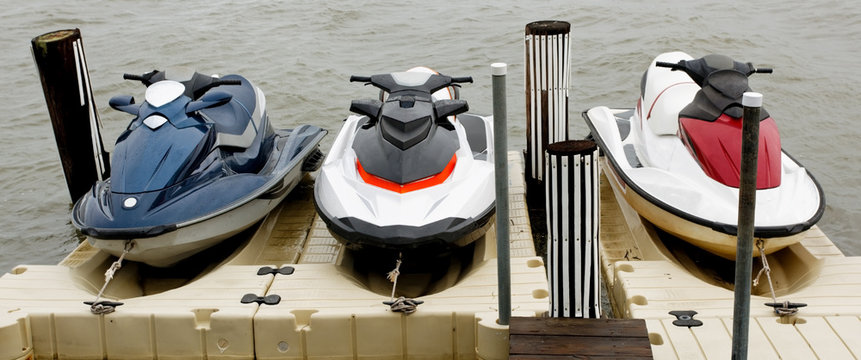 Three docked jet skis.