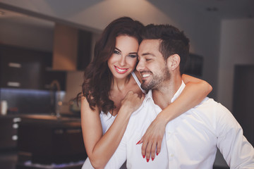 Young successful couple smiling, woman embrace man indoors